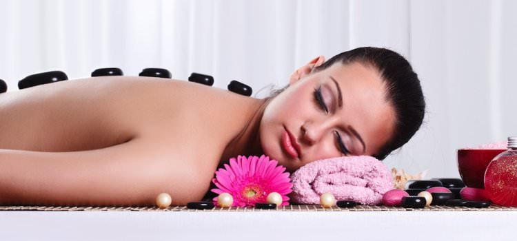 A picture of a woman receiving Hot Stone Massage therapy