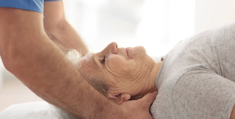Old woman receiving hospice care massage therapy