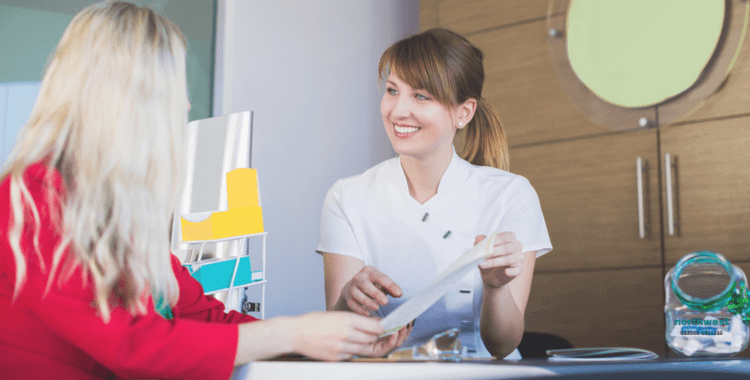 A Dental Administrative Assistant talking with client