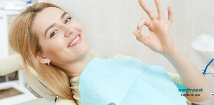 "young girl in a dental office giving the ""all-okay"" sign"