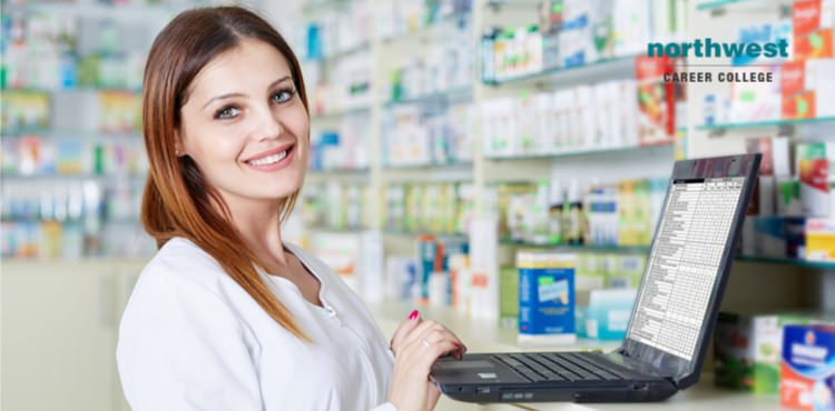 Pharmacy technician working with computer and smiling.
