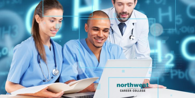 A group of people from medical field looking at computer and smiling.