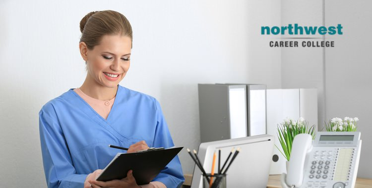 A medical administrative smiling ear-to-ear as she writes something on her clipboard.