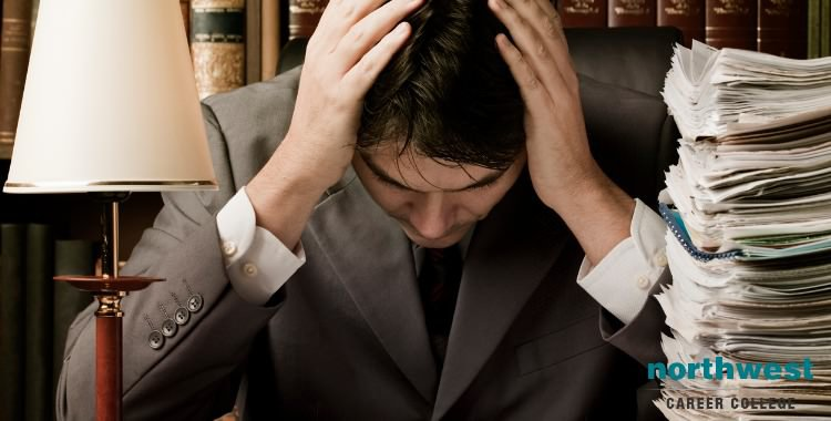 A paralegal is stressed, hand on his head, next to a stack of papers.