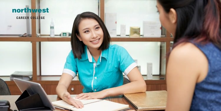 A female Medical Administrative Assistant Communicating with another woman.
