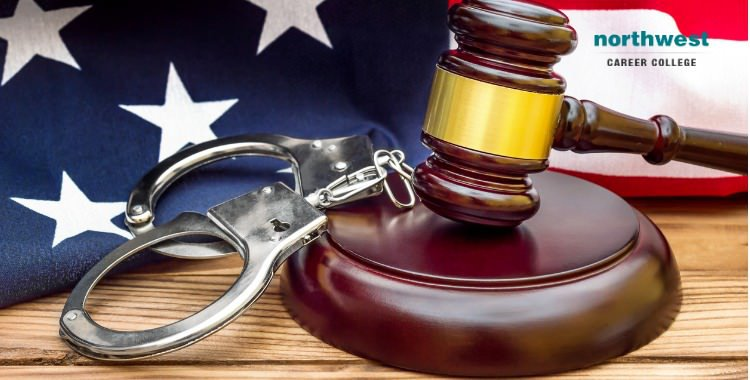 Gavel resting on a gavel-stand, handcuffs and American flag.