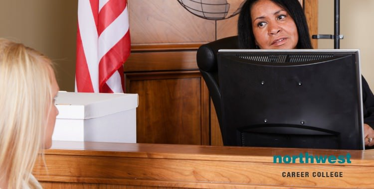 The court room using technology where a female judge is talking with a court clerk.