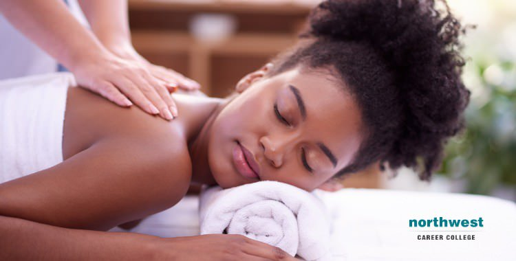 A woman taking massage therapy from a masseuse.