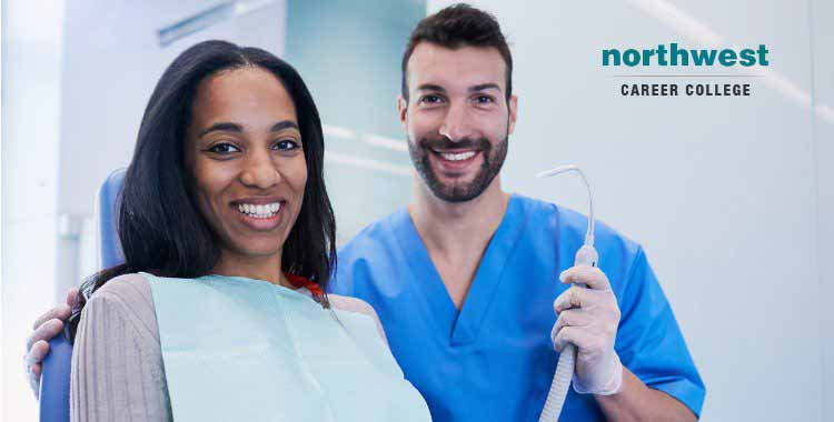 A dental assistant smiling with a woman patient