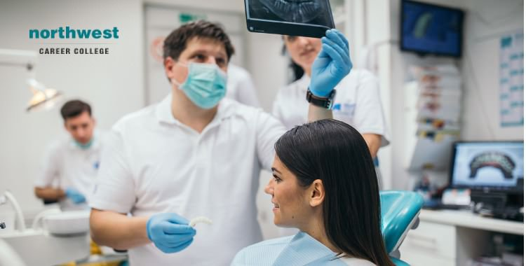 dental assistants looking at Xray of patient's teeth before procedure.