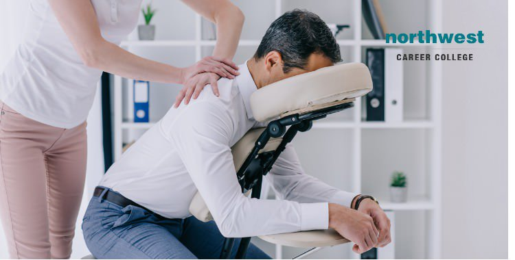 Man receiving massage from massage therapist in a specialized seat.