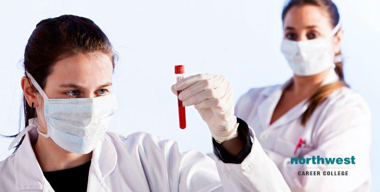 Female phlebotomist holding up blood sample in her left hand